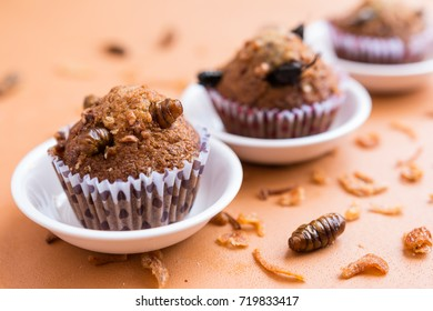Banana cupcakes with insect foods on the small white bowl and crispy shallots fried on orange tablecloth background. Healthy meal high protein diet concept.