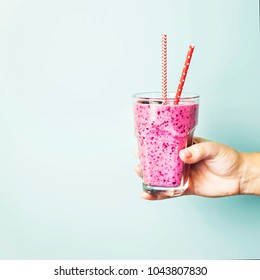 Banana currant smoothies of violet color with red straws on a blue background in the hand. Healthy food and diet concept . Background, copyspace
