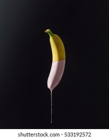Banana with dripping pink paint on dark background. Minimal food concept.