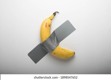 Banana duct taped to the white wall. Conceptual photo.