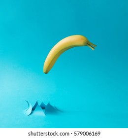 Banana fish jumping out of water made of paper. Minimal freedom concept.