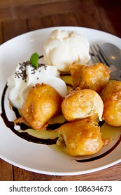 banana fritter with vanilla ice cream and whipcream and chocolate sauce
