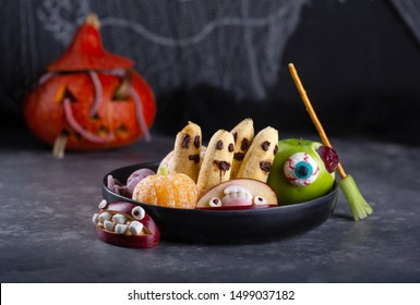Banana ghosts with chocolate faces, clementine pumpkins and apple monsters on black plate. Fruits in Halloween decoration on dark background.