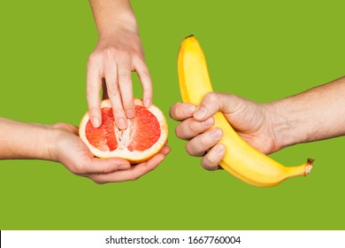 Banana and grapefruit in hands isolated on a green background as a symbol of male and female masturbation. Games with the clitoris and touching the penis. Stimulation and orgasm.