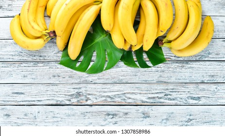 Banana with green leaves on a white wooden table. Tropical Fruits. Top view. Free copy space.