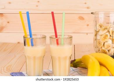 Banana juice and blender full of sliced fruits.