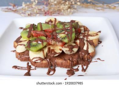 banana, kiwi and strawberry waffle with chocolate sauce. muz kivi ve çilekli waffle çikolata soslu - Shutterstock ID 1920037985