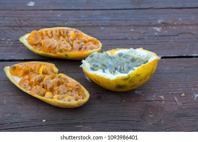 Banana maracuja and lemon maracuja fruits on wooden table, halved fruits ready to eat, fruit pulp with seeds