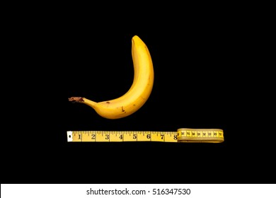banana and measuring tape on black background in concept of size does matter