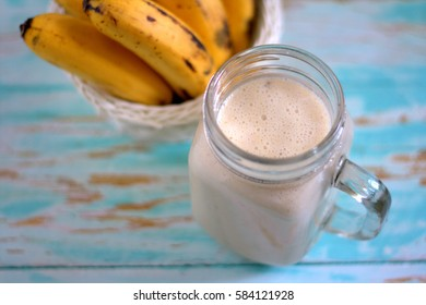 Banana milk shake on wooden table with banana on background. Purposely blur background and focus on milk.