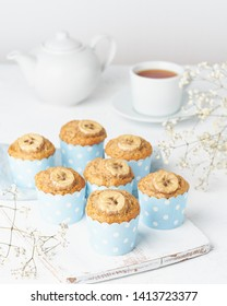 Banana muffin, cupcakes in a blue cake cases paper, side view, vertical, white concrete table