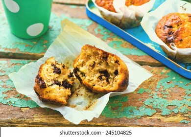 banana muffins with slices of chocolate and a glass with milk. style vintage. selective focus. the image is tinted