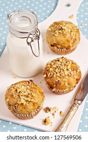 Banana muffins with walnuts and white chocolate and a bottle of milk on a cutting board