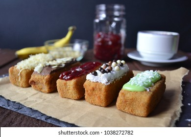 Banana nuggets. Pisang nugget. Delicious colorful banana nuggets on a stone board on brown wooden table on a dark background.