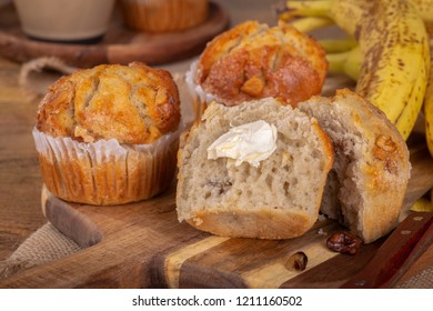 Banana nut muffin cut in half with butter and bananas in background