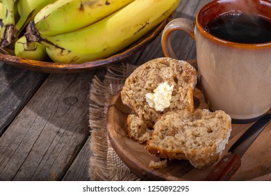Banana nut muffin cut in half with a cup of coffee on a wooden plate and a bowl of bananas in background