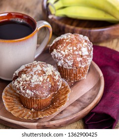 Banana nut muffins and cup of coffee on a wooden plate with  bananas in background