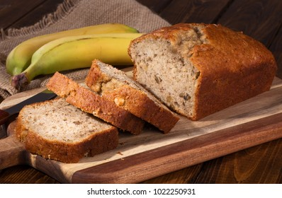 Banana nut sweet bread sliced on a wooden cutting board with bananas in background
