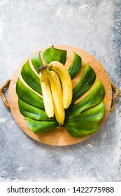Banana on a monstera leaf over a cutboard on a gray concrete background