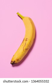 a banana on a pink background, half as it is actually, and half after a treatment, depicting the before and after a cosmetic surgery or beauty treatment, or before and after a digital retouching