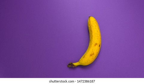Banana on purple background. Ripe fruit. One banana on a lilac background.