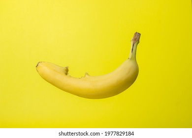 Banana on a yellow background. Bright fruit. Bitten banana with peel