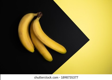 Banana on a yellow-black background. A bunch of bananas. Background for text. Tropical fruit. A healthy snack. Organic food. Healthy breakfast