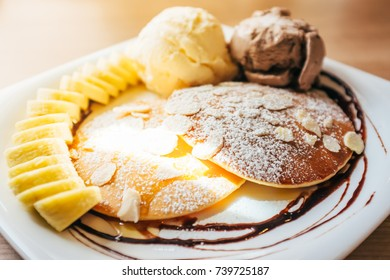Banana pancake topped with icing and chopped almond slice serve with vanilla and chocolate ice-cream, closeup of a pancake selective focus and with a very shallow depth of field.