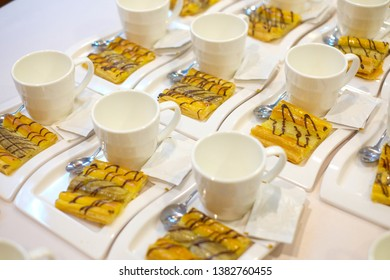 Banana Patty or 1 piece of pastry on a white plate.Have a glass placed beside.There is a lot placed on the table.concept:During a short break in the seminar