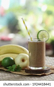 Banana, pear and lime smoothies in a glass with straw