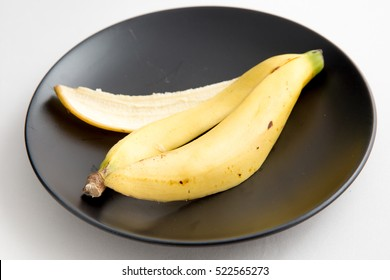 Banana peel  on a dish over white background