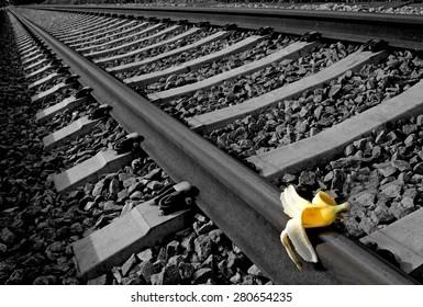 """Banana peel on railway.  """" Train Sabotage """" humoristic conceptual image."""