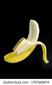 Banana peeled for eating on black background