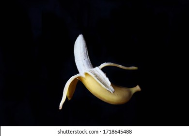 banana with peeled skin in a suspended position on a dark background