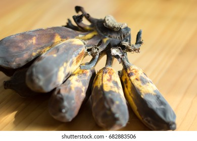 The banana rot on the wooden table with sunlight