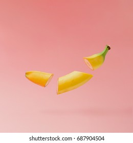 Banana sliced on pastel pink background. Minimal fruit concept.