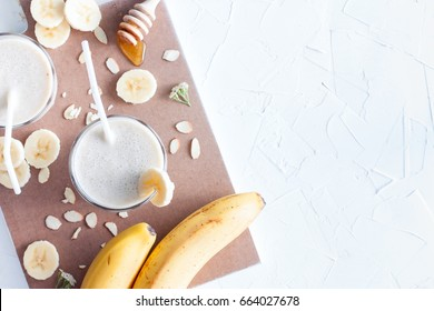 Banana smoothie with banana, milk, almonds and honey in glass glasses on a white table, top view, horizontal, selective focus