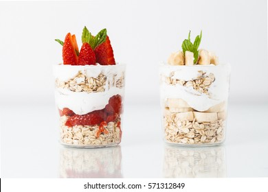 Banana and strawberry breakfast with oat in a jar on white background.