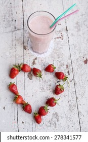 Banana and strawberry delicious smoothie with yogurt, on a wooden shabby background with two straws - mint and pink