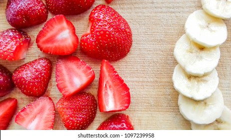 Banana and strawberry pieces on cutting board. Top view