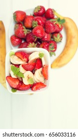 Banana strawberry salad cut into slices with mint leaves. Vitamin breakfast.