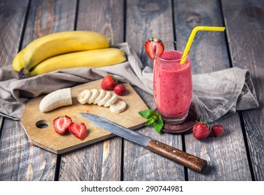 Banana and strawberry smoothie on wooden background
