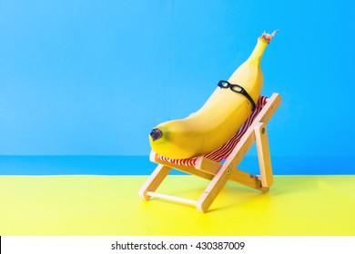 Banana con gafas de sol en la cama de sol. Concepto de vacaciones de verano.