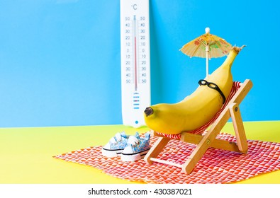 Banana with sunglasses on the sunbed with thermometer in the background. Summer holiday concept.