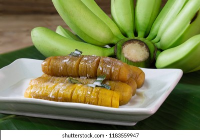 Banana in syrup with coconut milk and pandan leaf for smell in long white dish on green banana leaf / select focus and space for messags