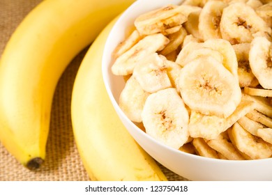 Banana - This is a close up shot of a bowl full of dried banana chips. Shot with a shallow depth of field and vignetting.