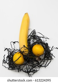 Banana and two lemons, symbol of phallus on white background, flat lay. Erection, sex, man power and potency concept.