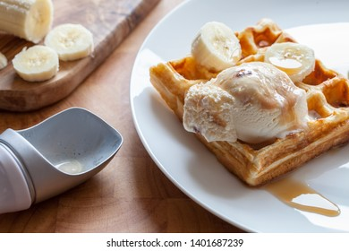 Banana waffle close-up. Delicious breakfast dessert meal prepared on plate. Sweet fried waffle with vanilla praline ice cream and maple syrup in close up on kitchen work surface.