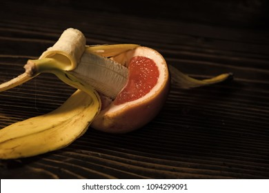 banana with yellow peel in red grapefruit on wooden background, sex and sexual intercourse, fruit love, vitamin and dieting, healthy food, penis and vagina