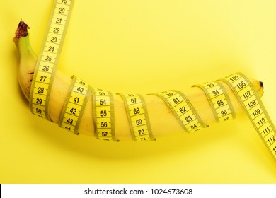 Banana with yellow tape for measuring figure. Rolled centimeter ruler spinned around fresh fruit. Fresh food and healthy diet concept. Yellow tape around banana isolated on yellow background.